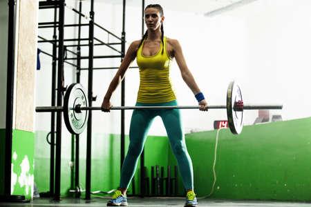 Jonge geschikte vrouw omhoog te trekken gewicht. Stockfoto - 62452514