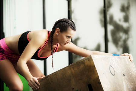 moving box: Young fit woman is moving jumping box.