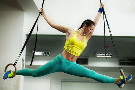 Young fit woman is using gymnastic rings. Stock Photo