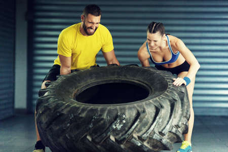 Young strong people on cross fit training. Flipping out tire. Stock Photo