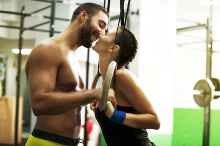Younf fit couple kissing in the gym. Stock Photo
