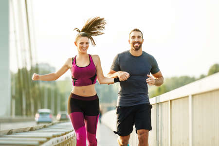 Happy couple running on the bridge.