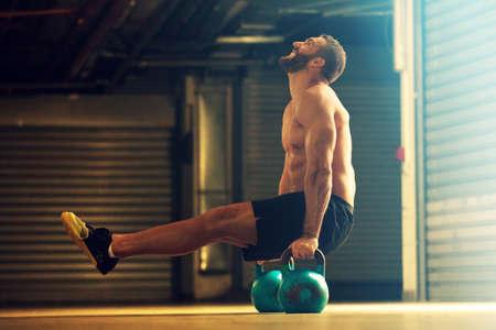 Jonge sterke man is training door kettlebell.