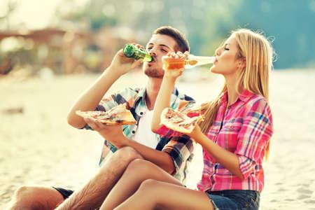 若いカップル、ビーチでピザを食べ、ビールを飲みます。