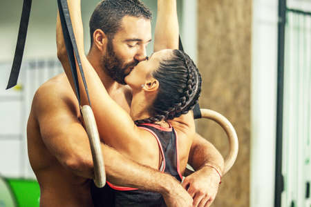 Young fit couple is kissing in the gym.