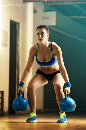 pullups: Fitness woman training by kettlebell.