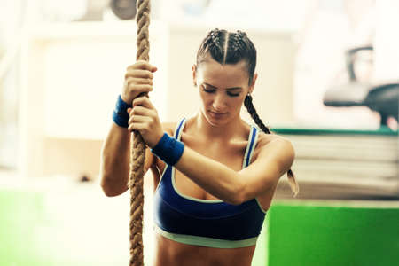 Young strong woman is climbing rope in gym.
