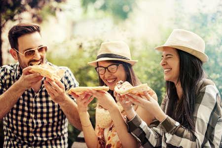 공원에서 재미와 피자를 먹고 젊은 사람들의 그룹.