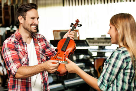 Yougn man is buying violin in musical instruments store. Stock Photo