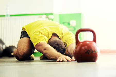 Fitness man is preparing for training by kettlebell.