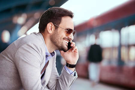 Young businessman is using phone on railroad station. Stock Photo