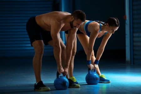 Fit man en vrouw opleiding door kettlebell. Stockfoto - 65157519