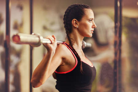 Young fit woman is training in gym.