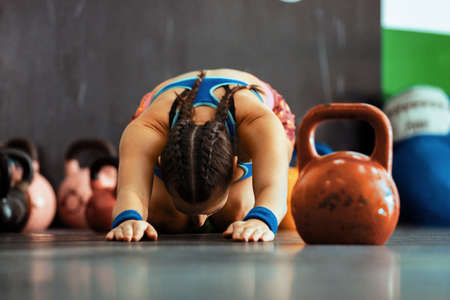 Young fitness woman training by kettlebell.