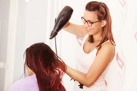 Red hair young woman at hairdresser.