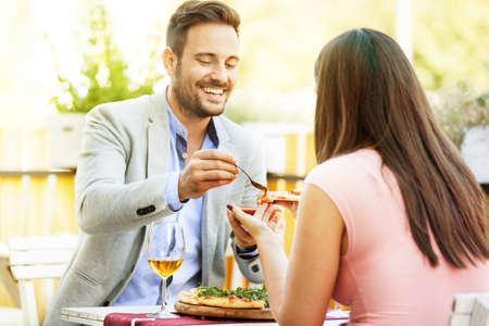 Šťastný pár jíst pizzu v restauraci. Selektivní zaměření na pizzu.