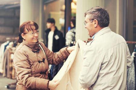 Senior couple enjoying shopping and buying blouse.