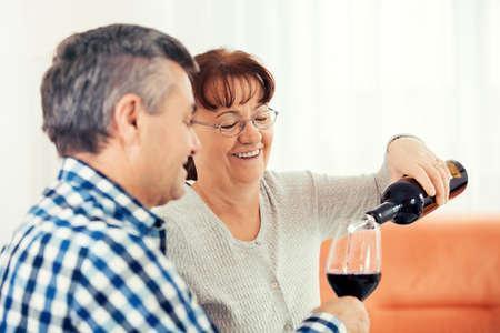 Senior couple enjoying living room and drinking wine.