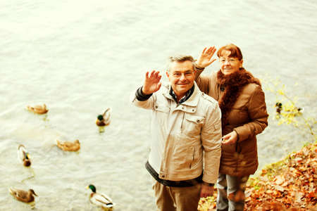 Happy senior couple feeding ducks on Thuns Lake Switzerland.