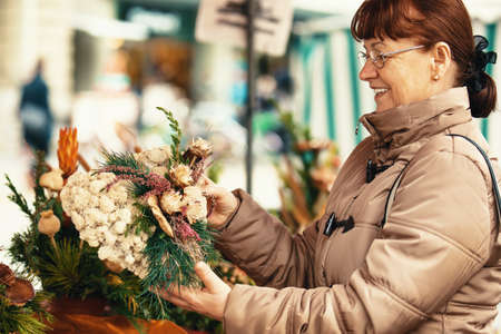 Senior woman is looking for Christmas decoration.