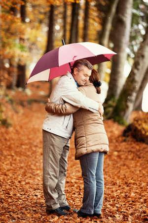 umbrela: Senior couple enjoying fall  in the forest.
