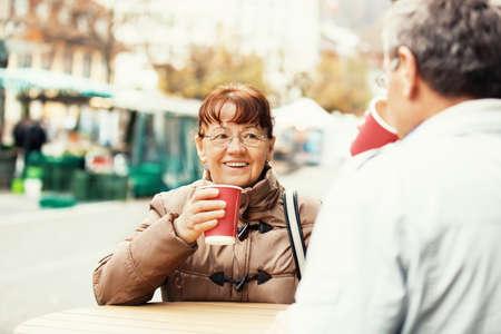 Senior couple enjoying coffee outside.