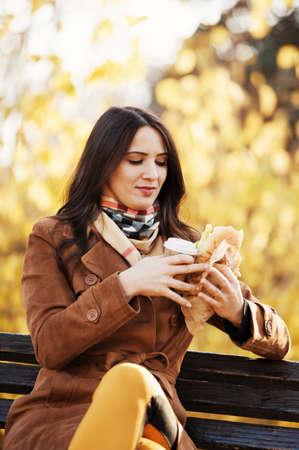 De mooie jonge vrouw heeft sandwich en hete drank in het park. Stockfoto