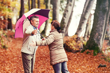 umbrela: Senior couple enjoying fall  in the forest.
