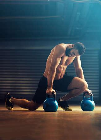 hombre joven de la aptitud es la formación de pesas rusas.
