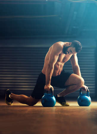 pullups: Young fitness man is training by kettlebell.