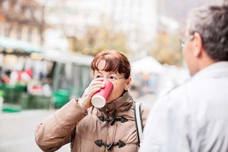 Senior couple enjoying outside and drinking coffee.