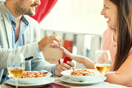 Engagement in a restaurant. Young man is giving a ring to his girlfriend.