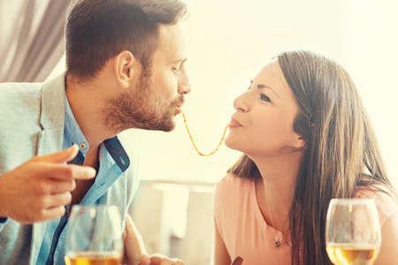 Happy couple enjoying food in an Italian restaurant. Love concept. Stock Photo