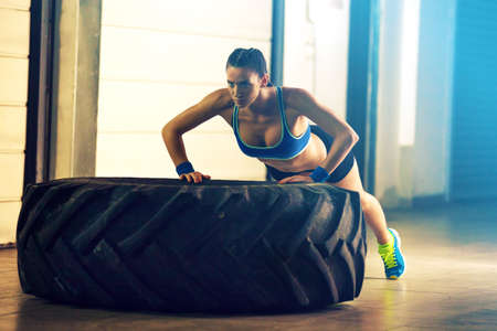 Fitness woman training by tire.