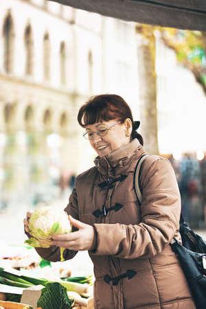 buying: Senior woman is buying cauliflower. Stock Photo