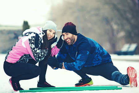 Young couple exercising outdoors on cold winter day.