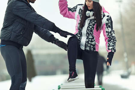 Young couple exercising outdoors on cold winter day. Stock Photo