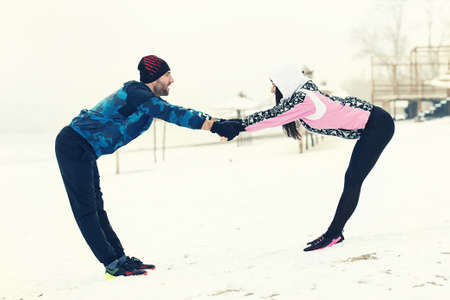 Sport couple exercising outdoors. Cold winter day.