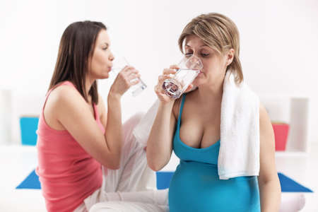 Pregnant woman and her trainer drink water after training. Living healthy lifestyle.