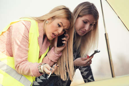 Two beutiful women having trouble with car. Calling for help.