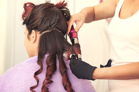 Young woman at hairdresser. Hairdresser is curling her hair. Stock Photo