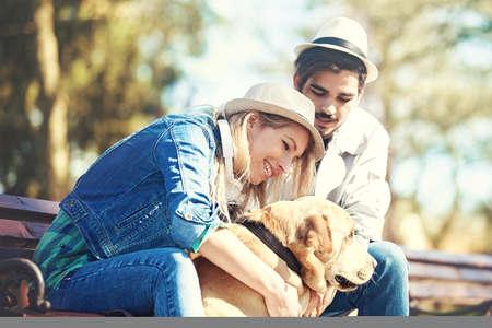 Jong en aantrekkelijk paar dat van de lente met Labrador geniet. Stockfoto - 74466672