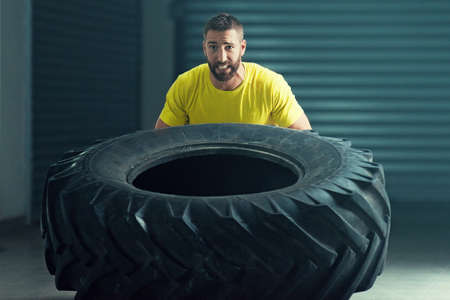 Young strong man is flipping out tire.