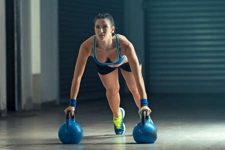 Fitness woman training by kettlebell in garage. Stock Photo