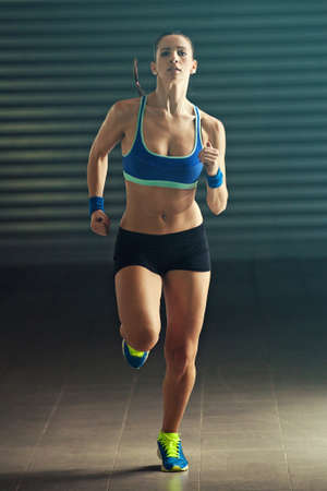 Fitness woman training and running in garage. Stock Photo