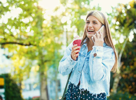 Happy young woman having fun in the city and eating icecream. Stock Photo