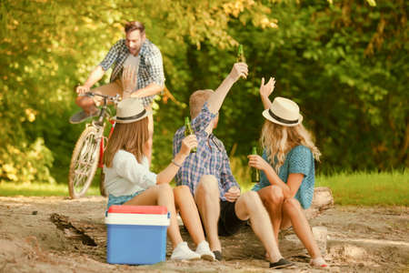 Group of friends is sitting on stump while their friend is coming with bike. Stock Photo