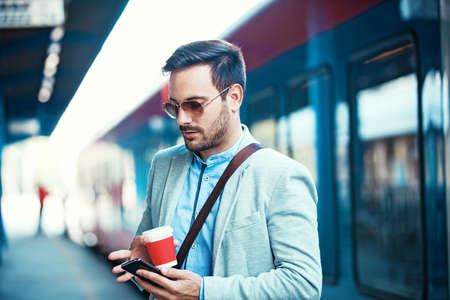 Young businessman on rail station using phone while waiting train. Stock Photo