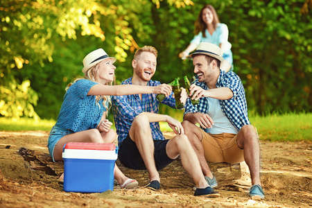 bear lake: Group of friends is sitting on stump while their friend is coming with bike. Stock Photo