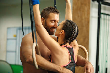 Young fit couple is enjoying in the gym. Stock Photo